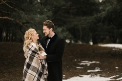 wedding couple look at each other while standing outside and hugging in winter and look each other