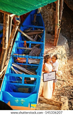 wedding couple near blue boat on exotic island