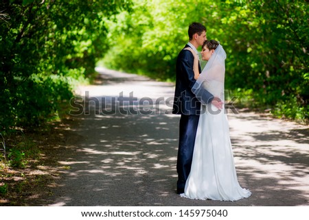Wedding couple newlywed bride and groom in love at wedding day outdoors. Happy loving couple at bridal day embracing. newlywed with bouquet flowers. Relationship. Smiling wife and husband kiss