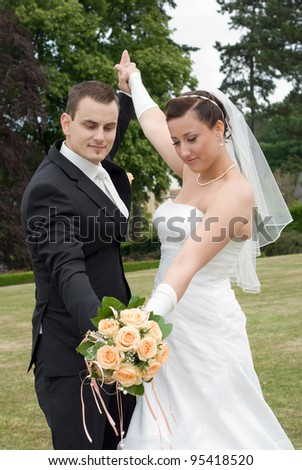 Wedding couple rising arms, look at bouquet