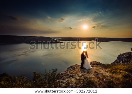 Wedding couple standing on the edge of a cliff. Groom tenderly embraces the bride. A beautiful seascape in the background.
