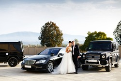 Wedding couple stands between E-clas and G-class Mercedes cars