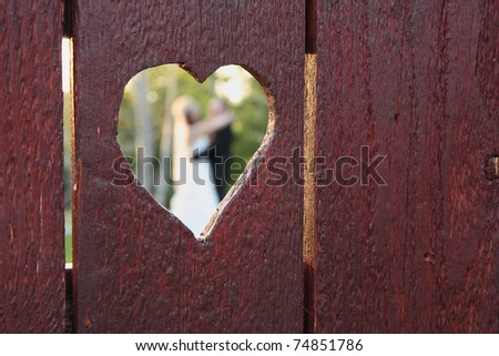 wedding couple viewed through heart-shaped hole in wood fence