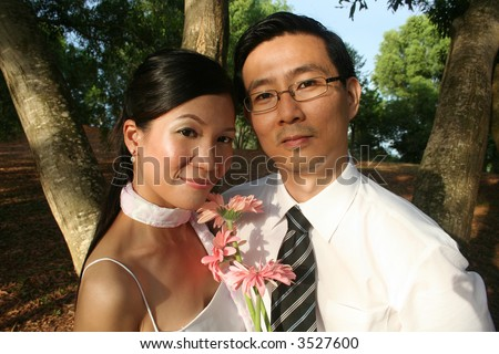 Wedding couple with pink daisy in the park