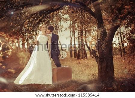 wedding couple with retro suitcase under fall season tree
