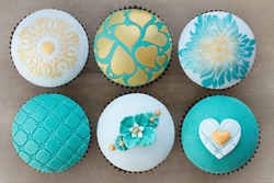 Wedding cupcakes decorated with teal and gold embossed fondant