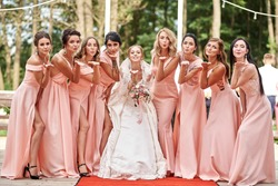 Wedding day. Beautiful bride and bridesmaids posing on the park on the wedding day. Bridesmaids dresses. Portrait of the bride and bridesmaids. wedding day after wedding ceremony