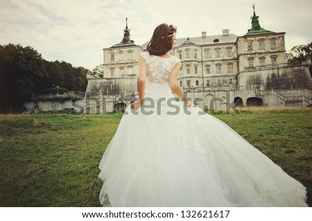 Stock Photo Wedding day. Gorgeous  bride walking next to castle in west Ukraine.