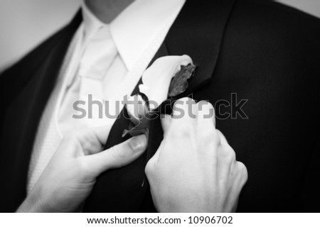 Wedding day groom and his boutonniere being pined