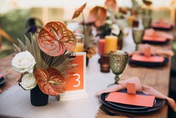 Wedding decor. Banquet. Glasses and plates, cutlery, candles and flower arrangements are on a wooden table in the garden