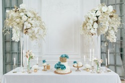 Wedding decor. Cakes and candles on white table