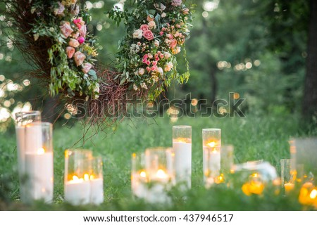 Wedding decor, candles in glass flasks in the forest.
