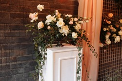 Wedding decor. Photographic area is a stylish wedding decoration. Decorated with flowers, mini florals. Wedding photo zone with flowers. Hand made wedding decorations. Place for taking pictures.