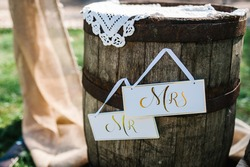 Wedding decor. Wooden barrel. Wooden plaque with the inscription Mr & Mrs. Wedding decorations signboard against the background of wooden box.