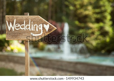 Shutterstock Wedding decor. Wooden plaque with the inscription Wedding. Wedding on a plate green background and a fountain. Wedding decorations,
