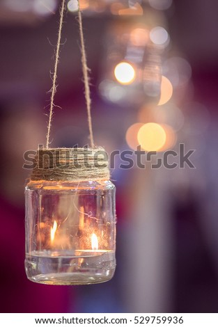 Wedding decoration in the form of glass jars with burning candles inside