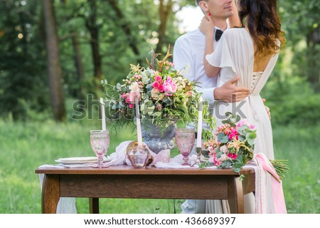 Wedding decoration in the style of boho, floral arrangement, decorated table in the garden. Against the background of the bride and groom embracing.