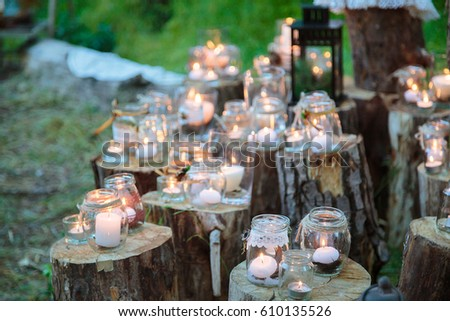 Shutterstock Wedding decorations in rustic style. Outing ceremony. Wedding in nature.  Candles in decorated jars