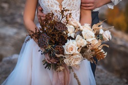 Wedding decorations. The groom hugs the bride, who is dressed in a white wedding dress and is holding a bridal bouquet of dried flowers. A beautiful bouquet of dry lotus and soft pink roses.