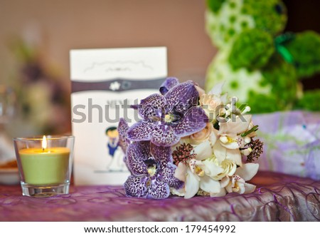 Wedding decorations with candle. Floral arrangements on wedding ceremony detail. Elegant wedding arrangement with flowers, candle and card