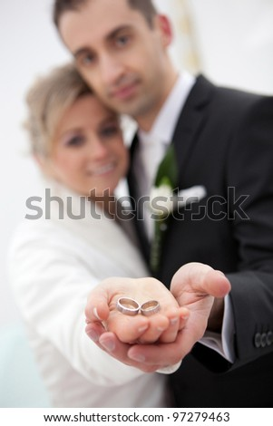 Wedding detail of the rings and hands holding