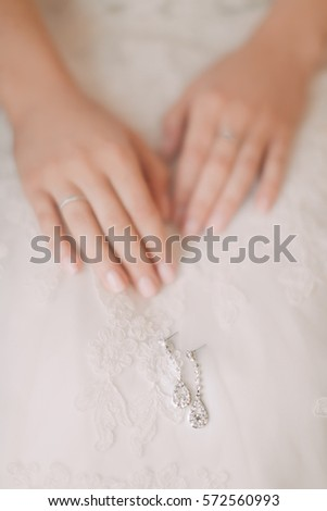 Wedding details. Wedding rings and wedding accessories on a background of the bride dresses. #572560993