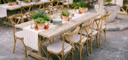 Wedding dinner table reception at sunset outside. Ancient rectangular wooden tables with rag runner, wooden vintage chairs, lavender pots, cherry tomatoes and clay pots with lemons on tables
