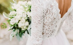 wedding dress. bride holds a wedding bouquet, wedding details