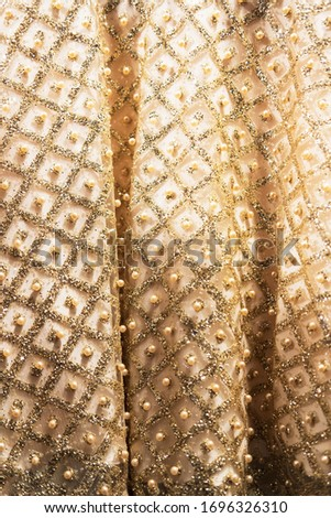 Wedding dress fabric texture background. Golden and ivory silk dress with beads, pearls, sparkles and embroidery. Vintage wedding dress detail. Elegant geometric pattern on fabric. Vertical, close up