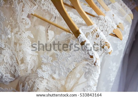 Wedding dresses hanging on a hanger. Fashion look. Interior of bridal salon. #533843164