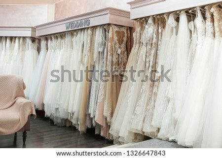 wedding dresses in store. wedding dresses hang in a row on hangers. large selection of wedding dresses in the Bridal fashion salon. wide choice of dresses.