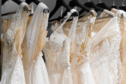 Wedding dresses made of silk chiffon, tulle and lace. Beautiful White cream bridal dress on hangers in wedding salon. Pearls and crystals pendants on the sleeves of a delicate color of a wedding dress