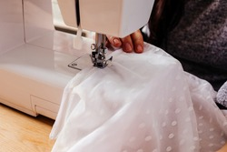 Wedding dressmaker altering white vintage wedding dress