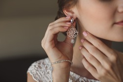 Wedding earrings on a female hand, she takes the earrings, the bride fees, morning bride, white dress, wear earrings