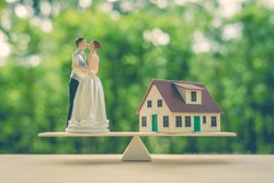 Wedding / eternal love concept  : Miniature figurine couple wedding doll, bride and bridegroom on balance scale with a model house, get married and carve out the future or build up a fortune together.