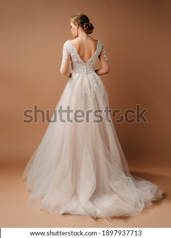Wedding fashion. Elegant brunette model in backless ivory lace wedding dress with long sleeves. Full-length studio portrait of young smiling bride. Photo stock ©