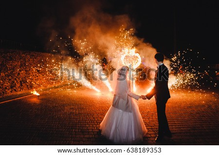 Wedding Fire show and fire heart at night on black background.Burning heart with fireworks. Brides holding hands and looking at fireworks and fire show.