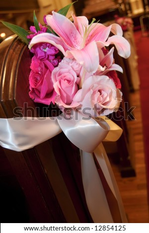 stock photo Wedding flowers in a church on the end of a pew
