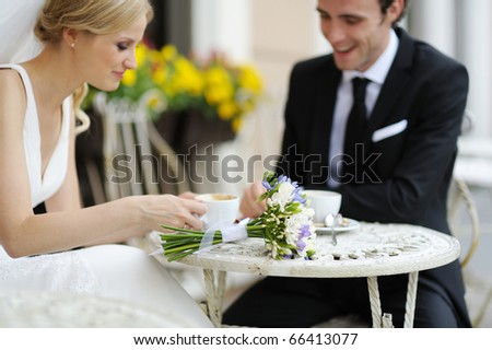 Wedding flowers on a table (bride and groom in a background)