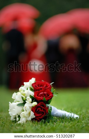 stock photo Wedding flowers on the grass and people with umbrellas in