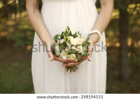 Wedding Flowers Roses Bouquet in Bride Hands with White Dress on Background