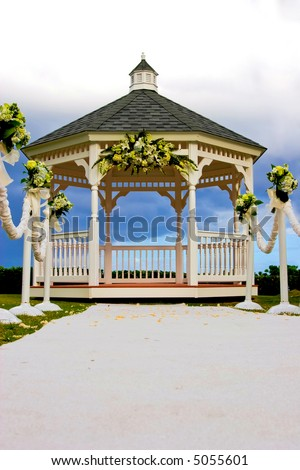 stock photo Wedding gazebo decorated with flowers and a white carpet isle
