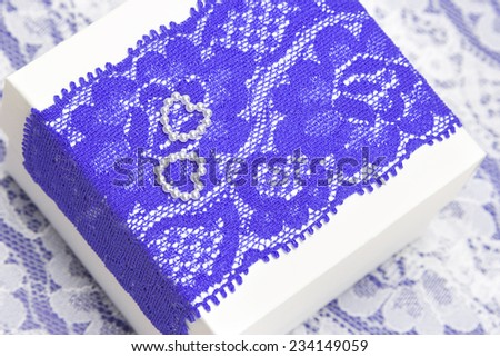 Wedding gift: white gift box decorated with violet lace and two small hearts made of beads. Shallow depth of field