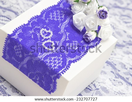 Wedding gift: white gift box decorated with violet lace, white satin roses and small hearts made of beads. Shallow depth of field