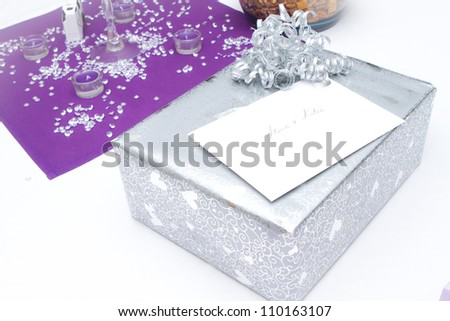 Wedding gifts on a plain white table with purple accent