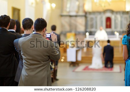 Wedding guest taking photos on a wedding ceremony