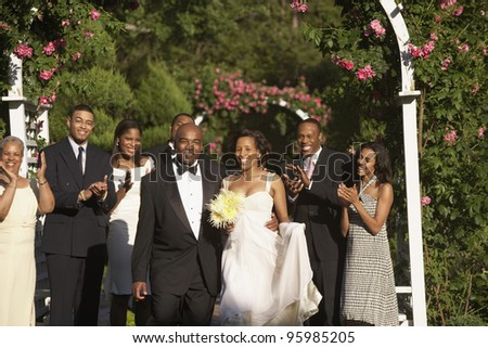 Wedding guests applauding newlyweds