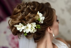 Wedding hair styling. Brown-haired bride with curly hairstyle with barrette. Wedding concept