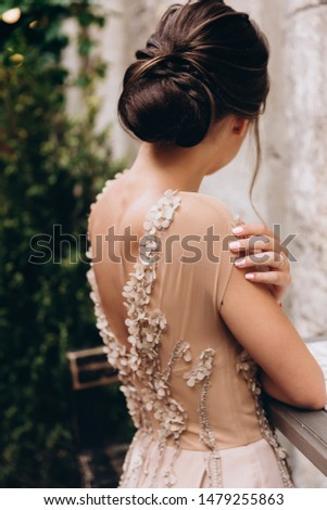 Wedding hairstyle, beautiful hairstyle bun, girl in a dress with a neckline on the back