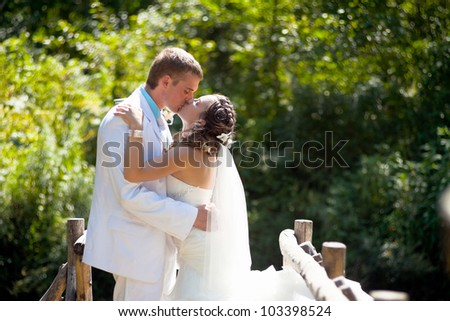 Wedding: Happy bride and groom kissing and hugging on green